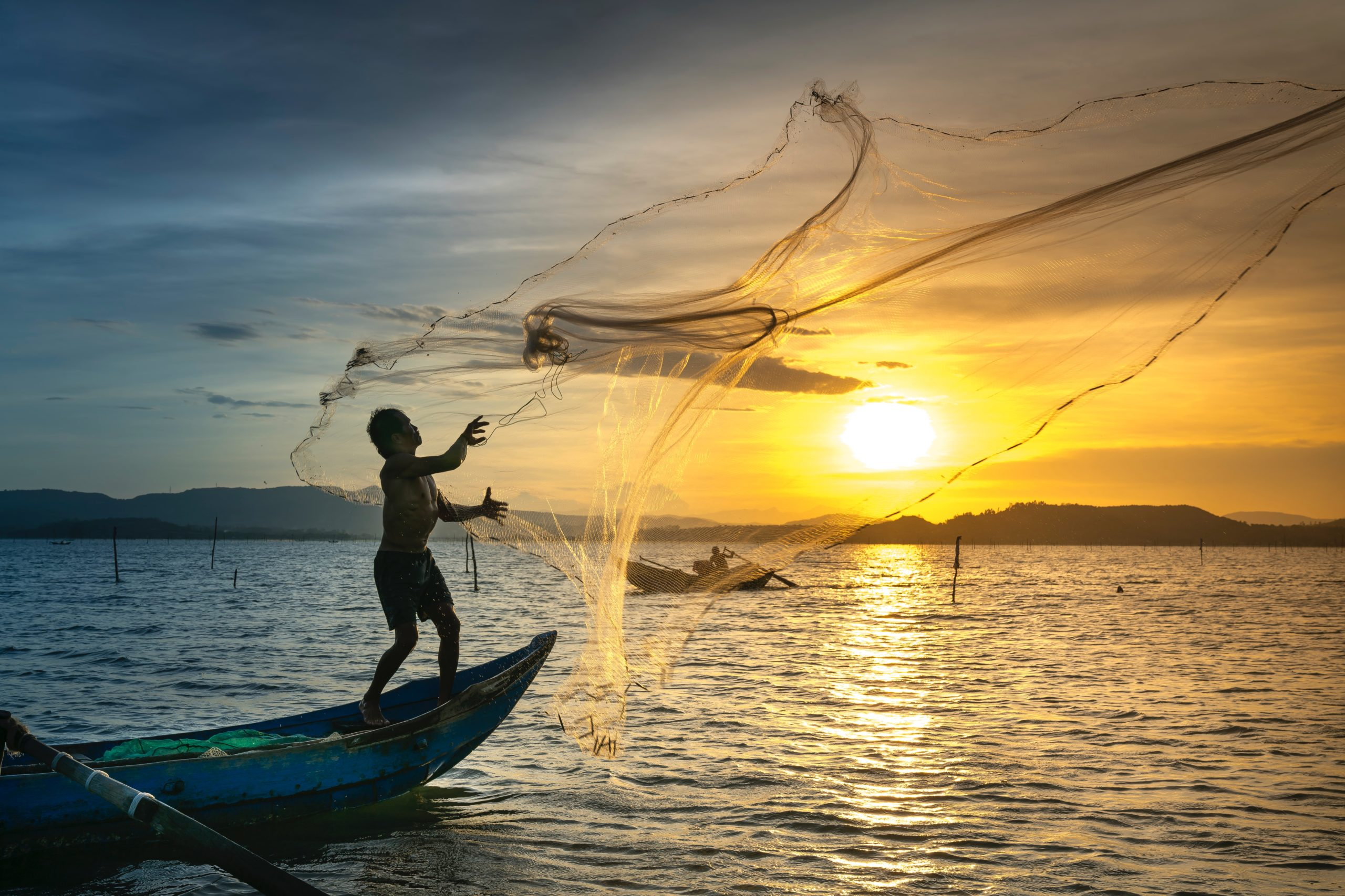 person throwing fish net while standing on boat scaled - Virtual Parks